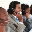 Stock Video: Happy call centre agents talking with their headsets