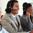 Stock Video: Happy call centre agents wearing headsets