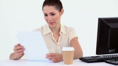 Zaměstnankyně čtení souboru u svého psacího stolu — Stock video