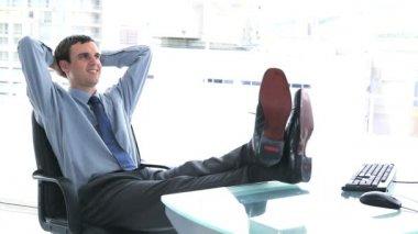 молодой предприниматель, отдыхая в своем кабинете — Стоковое видео