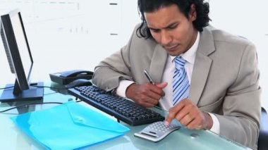 Businessman using a calculator while sitting a his desk — Stock Video