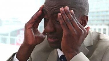 Black man in suit massaging his forehead — Stock Video