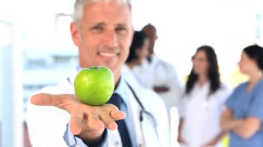 Smiling practitioner showing a green apple — Stock Video