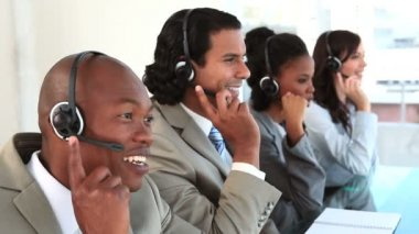 Happy call centre agents talking with their headsets — Stock Video