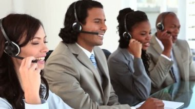 Happy call centre agents wearing headsets — Stock Video