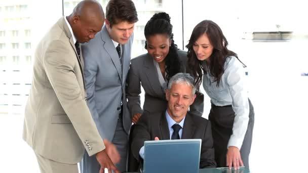 Equipo de negocios sonriente hablando alrededor de la computadora portátil — Vídeo de stock