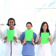 Smiling medical team showing blank papers — Stock Video