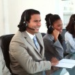 Stock Video: Happy call centre agents working with headsets