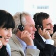 Stock Video: Joyful call centre agents sitting while wearing headsets
