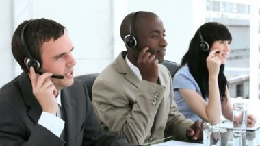 Smiling call centre agents working with headsets — Stock Video