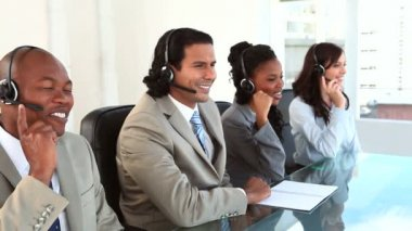 Happy call centre agents working with headsets — Stock Video