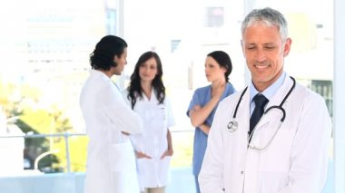 Smiling mature doctor standing upright in front of his team — Stock Video
