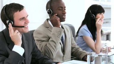 Happy call centre agents working together with headsets — Stock Video