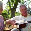 Retired man playing guitar to his wife - Stock Photo