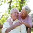 Retired woman embracing her husband - Stock Photo