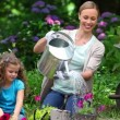 Mother watering flowers while her daughter is watching — Stock Video #20833207