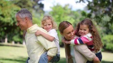 Rodzice zwracając się z dziećmi na plecach — Wideo stockowe