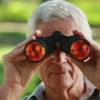 Smiling mature man looking through binoculars — Stock Video #20840191