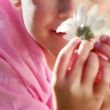 Stock Video: Peaceful little girl smelling flower