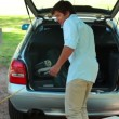 Father and son placing things in the trunk of the car — Vidéo
