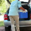 Rear view of a man placing his cooler in his car — Video