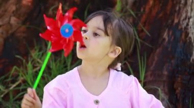 Happy little girl blowing on a pinwheel — Stock Video
