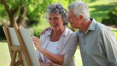 Smiling mature man looking at his wife who is painting — Stock Video