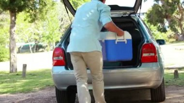 Rear view of a man placing his cooler in his car — Stock Video