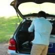 Father emptying the trunk of the car with his family — Vídeo Stock