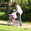 Smiling woman helping her daughter to ride a bike — Stock Video #20867581