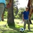 Stock Video: Smiling man playing with a soccer ball with his son