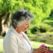 Smiling mature woman being given a flower — Stock Video