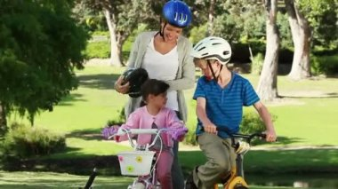 Smiling mother fastening the helmets of her children — Stock Video