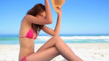 Happy brunette woman sitting on the sand while holding her hat — Stock Video