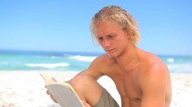 Ciddi sarışın adam bir roman okuma — Stok video