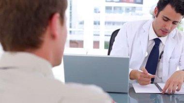 Poważne lekarz mówi do jego pacjent siedząc — Wideo stockowe