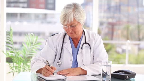 Docteur mature souriante, parler au téléphone — Vidéo