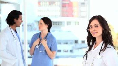 Colleghi parlando dietro un medico — Video Stock