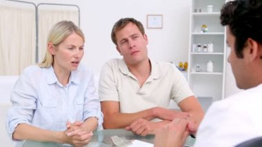 Disappointed couple sitting in front of their doctor — Stock Video