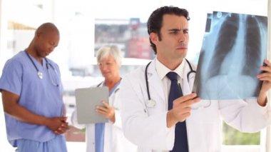 серьезные доктор, глядя на рентген грудной клетки стоя — Стоковое видео