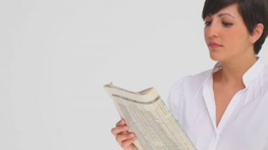 Businesswoman nods as she reads a newspaper — Stock Video
