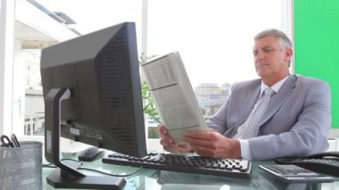 Businessman smiling as he reads a newspaper — Stock Video