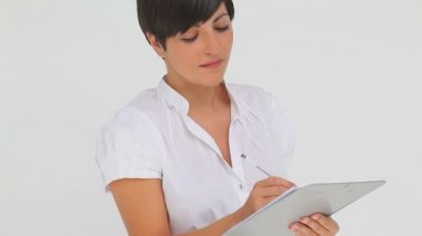Businesswoman smiling while writing on a clipboard — Stock Video