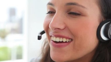 Businesswoman smiles as she talks on a headset — Stock Video