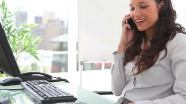 Businesswoman smiles as she answers a phone — Stock Video