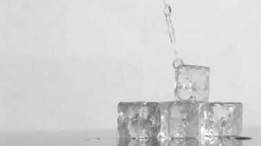 Trickle of water in a super slow motion flowing on ice cubes and falling it — Stock Video