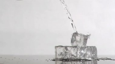 Trickle of water in a super slow motion flowing on ice cubes — Stock Video