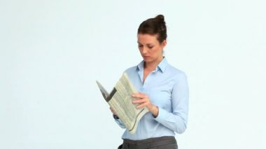Woman reads a newspaper and crosses her arms — Stock Video