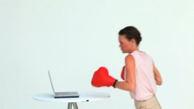 Businesswoman hitting a laptop with boxing gloves — Stock Video