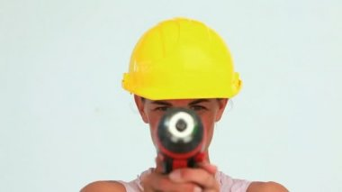 Businesswoman with safety helmet blowing on a screw gun — Stock Video